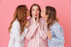 Le portrait trois du jeune habillement à la maison de port intéressant des filles 20s étreignent Photos libres de droits