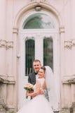 Le portrait vertical des nouveaux mariés de sourire se tenant dans l'avant de la vieille maison Photo stock