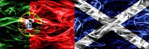 Le Portugal contre l'Ecosse, drapeaux écossais de fumée placés côte à côte Drapeaux soyeux colorés épais de fumée de portugais et image libre de droits
