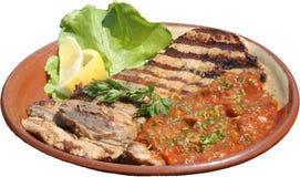 Le porzioni di bistecca arrostita sono servito con le verdure dell'arrosto e della salsa al pomodoro Fotografia Stock