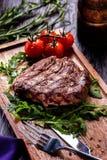 Le porzioni succose di filetto di bue arrostito sono servito con i pomodori e immagini stock libere da diritti