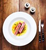 Le porzioni succose di filetto di bue arrostito sono servito con i pomodori, sau Fotografie Stock