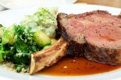Le porzioni succose spesse di filetto di bue arrostito sono servito con verde Immagine Stock