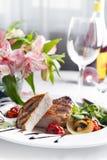 Le porzioni succose spesse succulenti di filetto di bue arrostito sono servito con i pomodori e le verdure dell'arrosto Fotografia Stock Libera da Diritti