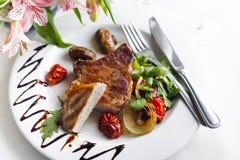 Le porzioni succose spesse succulenti di filetto di bue arrostito sono servito con i pomodori e le verdure dell'arrosto Immagini Stock Libere da Diritti