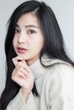 Le pose asiatiche della ragazza trattano il suo mento fotografia stock libera da diritti