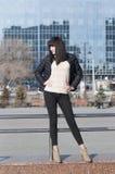 Le pose della giovane donna contro lo sfondo delle costruzioni moderne Fotografie Stock