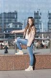 Le pose della giovane donna contro lo sfondo delle costruzioni moderne Fotografie Stock Libere da Diritti