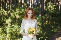 Le pose della sposa del redhair in foresta Immagine Stock
