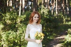 Le pose della sposa del redhair in foresta Fotografia Stock