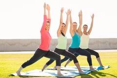 Le poserar sportiga kvinnor som gör krigaren, i yogagrupp royaltyfri bild