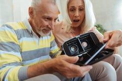 Le positif étonné a vieilli des couples essayant vers le haut des verres de VR Image stock