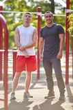 Le positif folâtre des amis d'hommes sur un fond brouillé de parc Concept confortable de vêtements de sport Photographie stock libre de droits