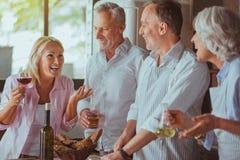 Le positif a vieilli des amis étant prêts pour le dîner de fête Image stock