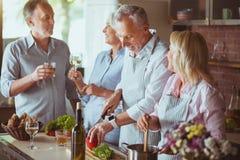 Le positif a vieilli des amis se reposant ensemble dans la cuisine Image libre de droits