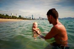le postérieur de père enseigne la fille à nager en eau de mer peu profonde Images libres de droits
