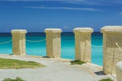 le poste coloniali della pietra di stile su una scogliera orlano l'oceano Immagine Stock
