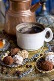 Le pot de café verse le café dans la tasse dans le style oriental sucreries faites main, fruits secs et fleurs photo dans images stock