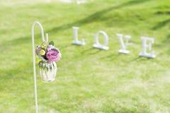 Le pot de fleur décorent dans le lieu de rendez-vous de mariage dans le jardin avec amour se connectent Photos stock