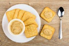 Le pot de fromage fondu, de cuillère à café et de biscuits a enduit le fromage fondu photos libres de droits