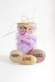 Le pot de pétales de fleur avec heureux, aiment et embrassent des roches Photo stock