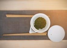 Le pot de thé vert et 2 paires de baguettes en bois sur le gris vêtent le tapis sur la table en bois photos stock