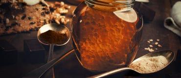 Le pot de vrai miel sain avec le nid d'abeilles à l'intérieur, chocolat trouble Image libre de droits