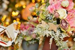 Le pot des roses et de l'hortensia roses neigeux en tant qu'arbre de décoration de Noël sur le bokeh s'allume Photographie stock