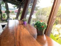 Le pot en plastique avec la fleur sur la table en bois sont décoration Photo stock