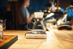 Le pot en verre de café se tient sur le plan rapproché de fourneau, personne images stock