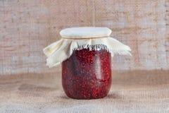 Le pot en verre de confiture de framboise est une Photo stock
