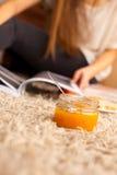 Le pot en verre ouvert avec de la confiture douce d'abricot est sur le plancher photos stock