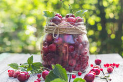 Le pot en verre porte des fruits des cerises et des framboises Images stock