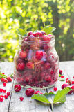 Le pot en verre porte des fruits des framboises de cerises Photo stock