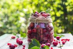 Le pot en verre porte des fruits des framboises de cerises Image stock
