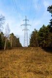 Le poteau à haute tension dans la ligne transfert courant de forêt photos stock