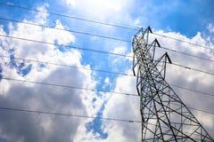 Le poteau électrique et le fil de tour à haute tension avec les nuages et le soleil de ciel bleu s'allument Image stock
