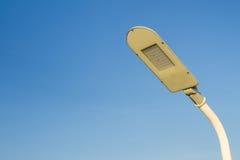 Le poteau d'énergie d'économies de lampe de réverbère avec un backgroun de ciel bleu Image libre de droits