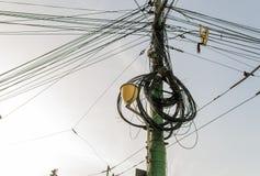 Le poteau de l'électricité et le réverbère ont compliqué le câblage sur le poteau image stock