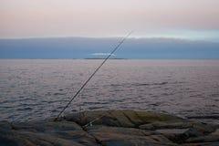 Le poteau de pêche est sur un rivage rocheux Image libre de droits
