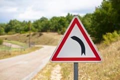 Le poteau de signalisation indiquant la route tourne à gauche Photographie stock