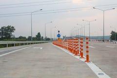Le poteau orange du trafic ou la borne flexible du trafic sur la route goudronn?e pour le carrefour image libre de droits