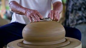 Le potier asiatique de plan rapproché rectifie le grand pot en céramique avec l'anneau en métal banque de vidéos