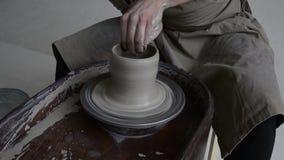 Le potier crée le produit sur une roue du ` s de potier sur la poterie de rotation de tour du ` s de potier banque de vidéos