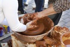 Le potier enseigne faire cuire des bacs son aide. photo stock