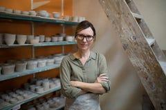 Le potier féminin se tenant avec des bras a croisé dans l'atelier de poterie photos libres de droits