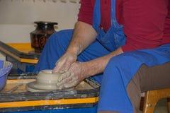 Le potier fait sur la cruche d'argile de roue de poterie Photos stock