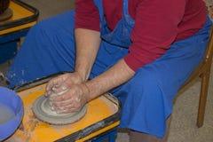 Le potier fait sur la cruche d'argile de roue de poterie Les mains d'un potte Image libre de droits