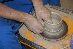 Le potier fait sur la cruche d'argile de roue de poterie Les mains d'un potte Photographie stock
