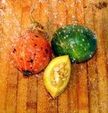 Le potiron et la pastèque mûrs de coupe se trouvent sur un conseil en bois sous les gouttes de l'eau images stock